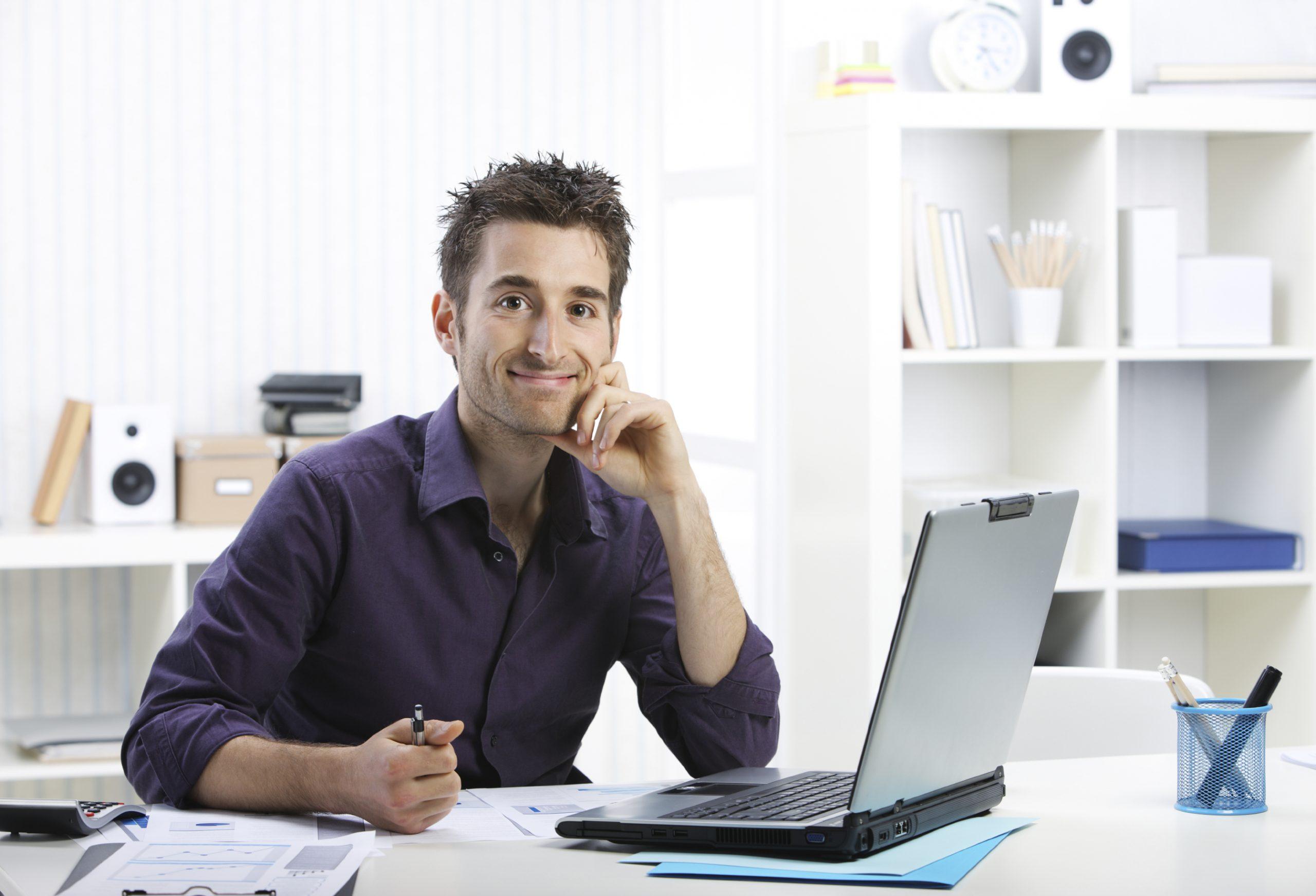 Guy Smiling at Laptop  Desk  scaled - Como funciona o suporte